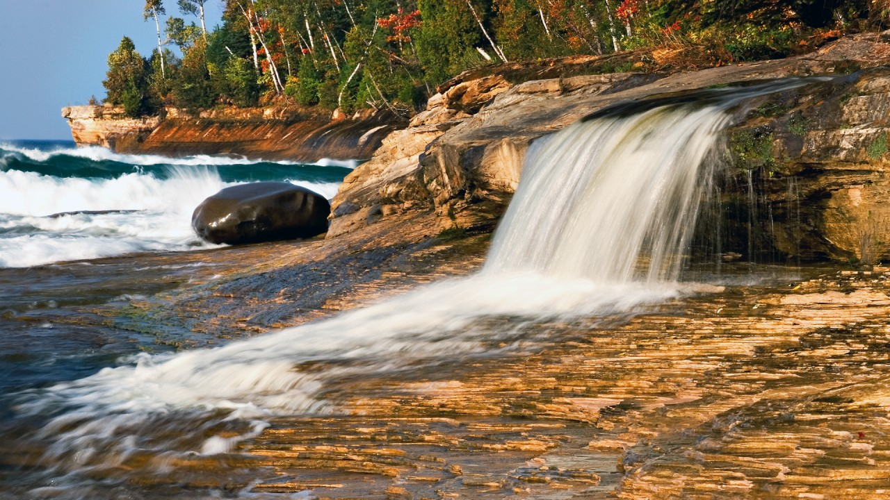 A Lake Michigan waterfall empties over a bed of rocks