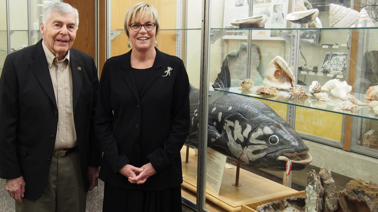 Museum founder and a former student stand next to a coelacanth exhibit