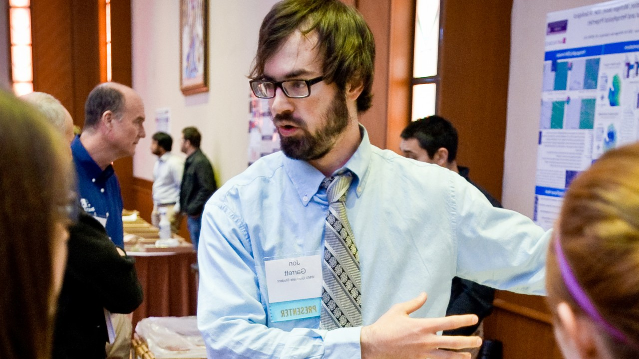 A graduate student presents his research poster at a PTTC workshp
