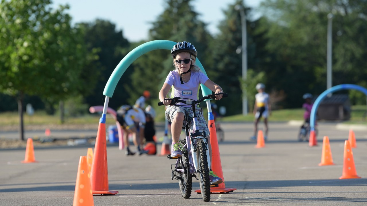 Young girl on bike riding through obstacle course