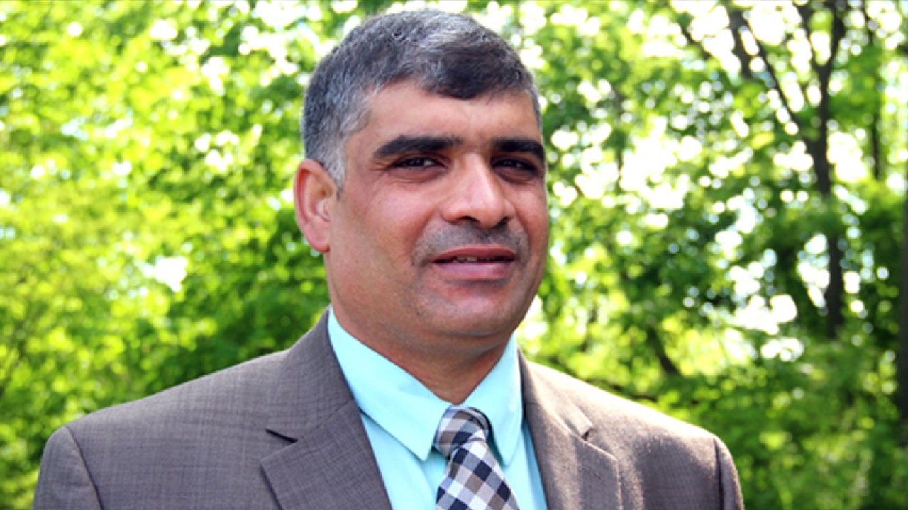 A photo of Electrical and Computer Engineering student Amer Chlaihawi. Mr Chlaihawi is standing in front of a wooded background. He has short, distinguished black hair with grey highlights. He is wearing a nice suit with a blue button-up shirt and plaid tie.