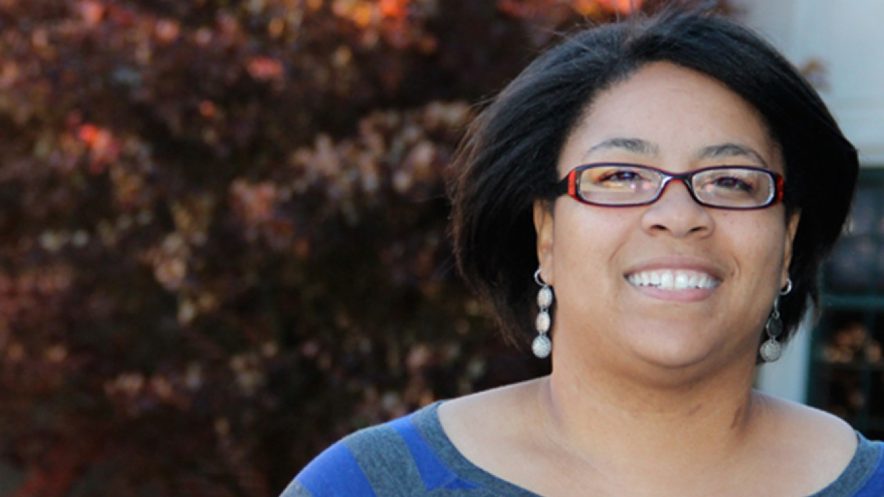 A photo of Geosciences student Denisha Griffey.  Denisha has a happy yet thoughtful expression.  She has shoulder-length black hair, and is wearing translucent red glasses and some dangling earrings that have three groups of small stones arranged in circular patterns.  She is wearing a purple and grey striped blouse, and standing in front of Walwood hall. In the background is a tree with reddish leaves that signify the season of autumn.