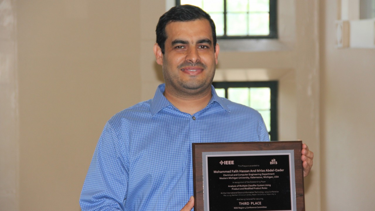 A photo of Mohammed Hassan, doctoral student in Electrical and Computer Engineering. Mr. Hassan has short black hair, a warm smile, and wearing a blue and white striped button-up shirt.  He is holding a plaque that recognizes his third-place achievement at the 2015 I E E E International Conference on Electro/Information Technology (EIT).