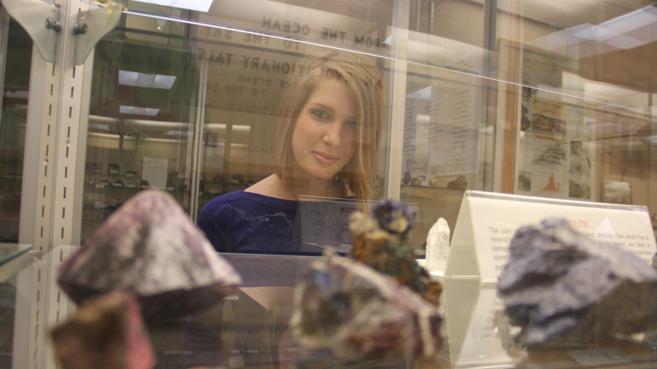 A Geosciences student observes a variety of rock samples displayed in a display case.  Among the samples are purple and reddish naturally forming crystals.