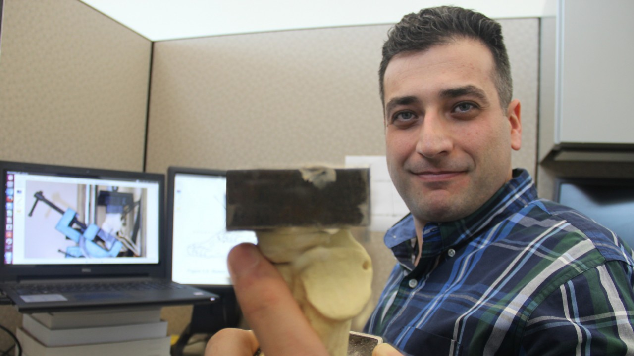 a photo of Saif Alrafeek.  Saif is holding a piece of engineered bone which has square metal plates attached on each end.  Different bone repair materials will be attached to the bone, and then the sample will be stress tested with pulling and or crushing forces. The best repair materials may go on to be used in surgery repair with real bones.