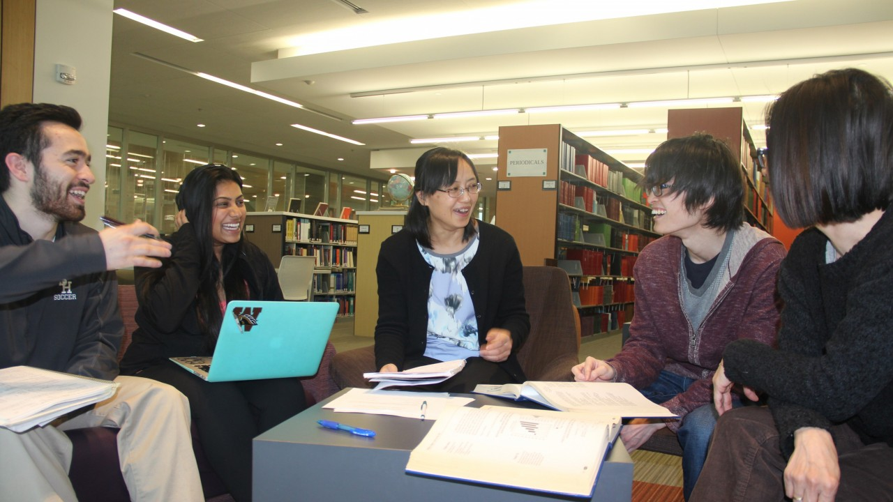 A group of students is shown studying in the education library of Sangren hall. A bearded man sits on the left and motions with his hand as he is speaking. A woman with long black hair and a teal colored laptop sits next to him.  In the center leading the group Is Yu Du, a graduate student from China.  Next to her are a man and a woman, both have books open as they discuss their subject.