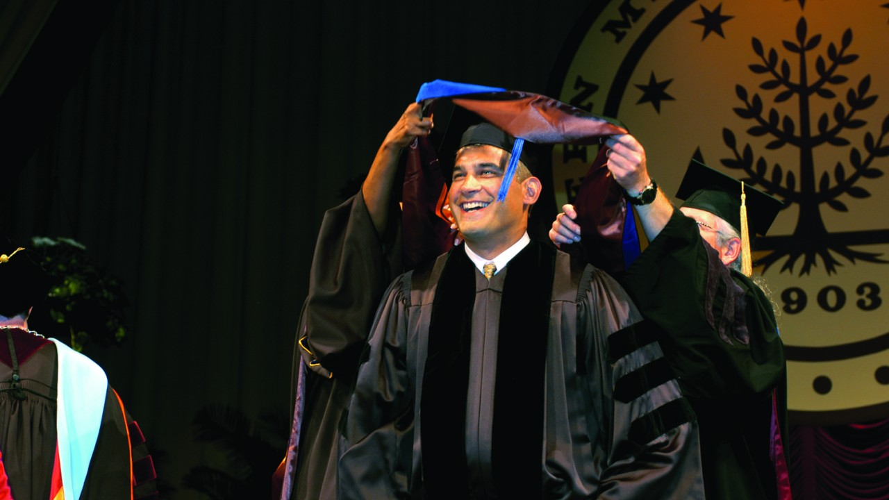 This photo is of a man receiving his doctoral hood at a W M U commencement ceremony.  He wears the traditional square black mortarboard hat and a black graduation robe.  His robe has three black velvet stripes on each sleeve and wide black velvet trim in the front along the zipper closure which makes it stand out in comparison to a traditional bachelor's degree robe.