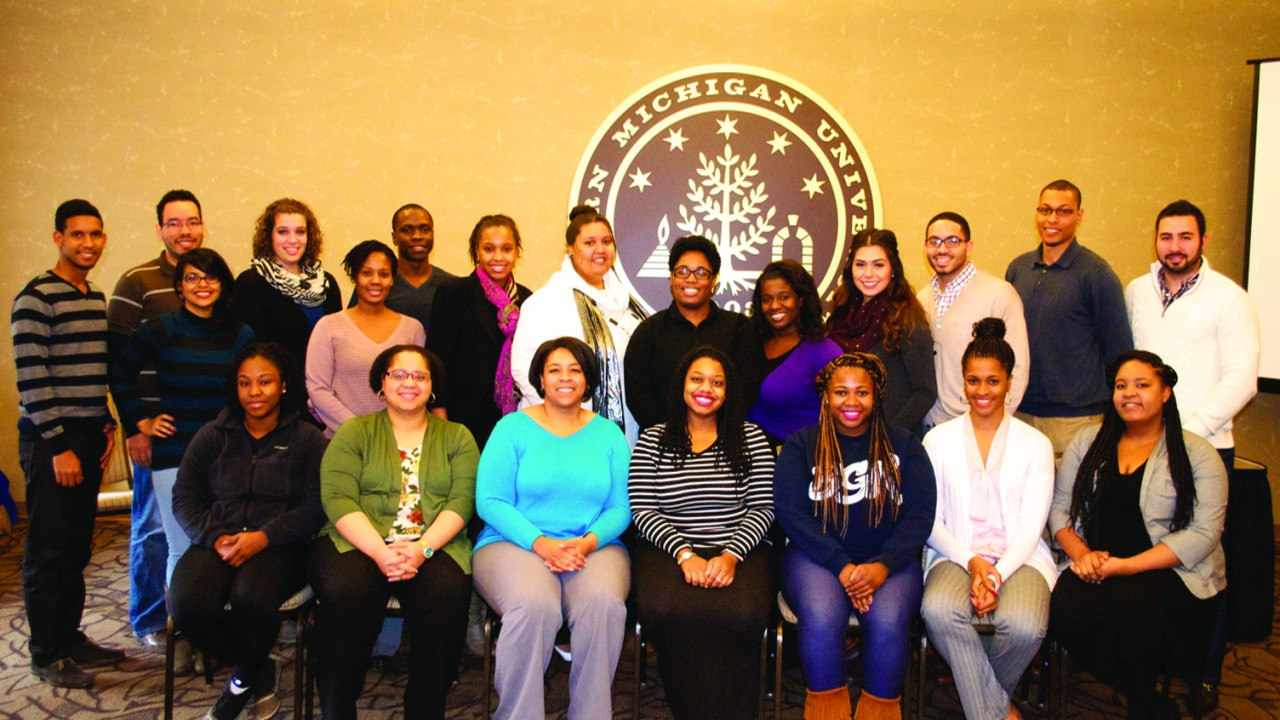 A group of twenty one students pose for a photo at a recent W M U alliance for graduate education and professoriate meeting.  The group is notably diverse with African American, latino, and caucasians represented. Seven of the students are seated in chairs with the remainder crowded in behind. This photo was taken inside, but you can tell that it is in the winter as you can see a few warm jackets and many of the women are wearing scarves.