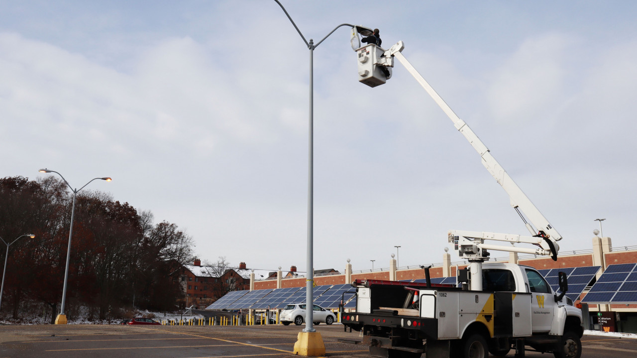 Photo of a bucket truck that is parked in a parking lot while an employee repairs a light pole with the bucket lifted. Solar panels and a couple cars fill the background.