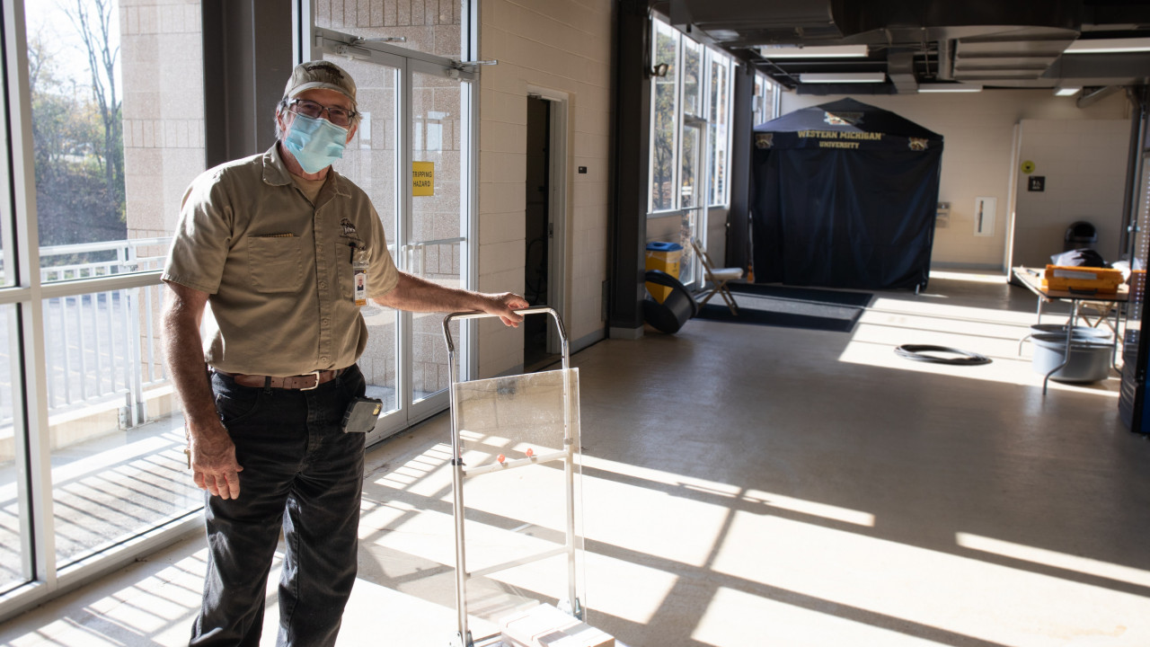 Photo of employee standing in a room, looking at the camera with hand on a utility cart that contains plexiglass shields
