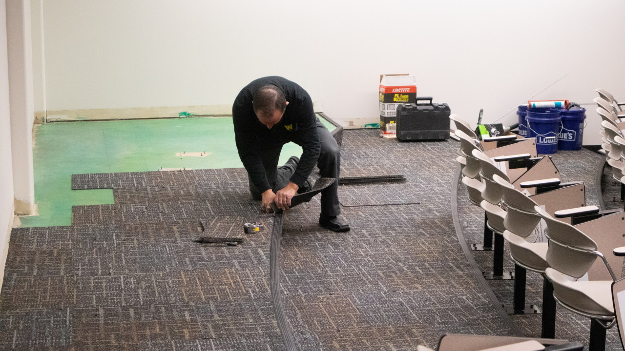 Photo of employee installing neutral colored carpeting in a tiered classroom with tools and materials in the background
