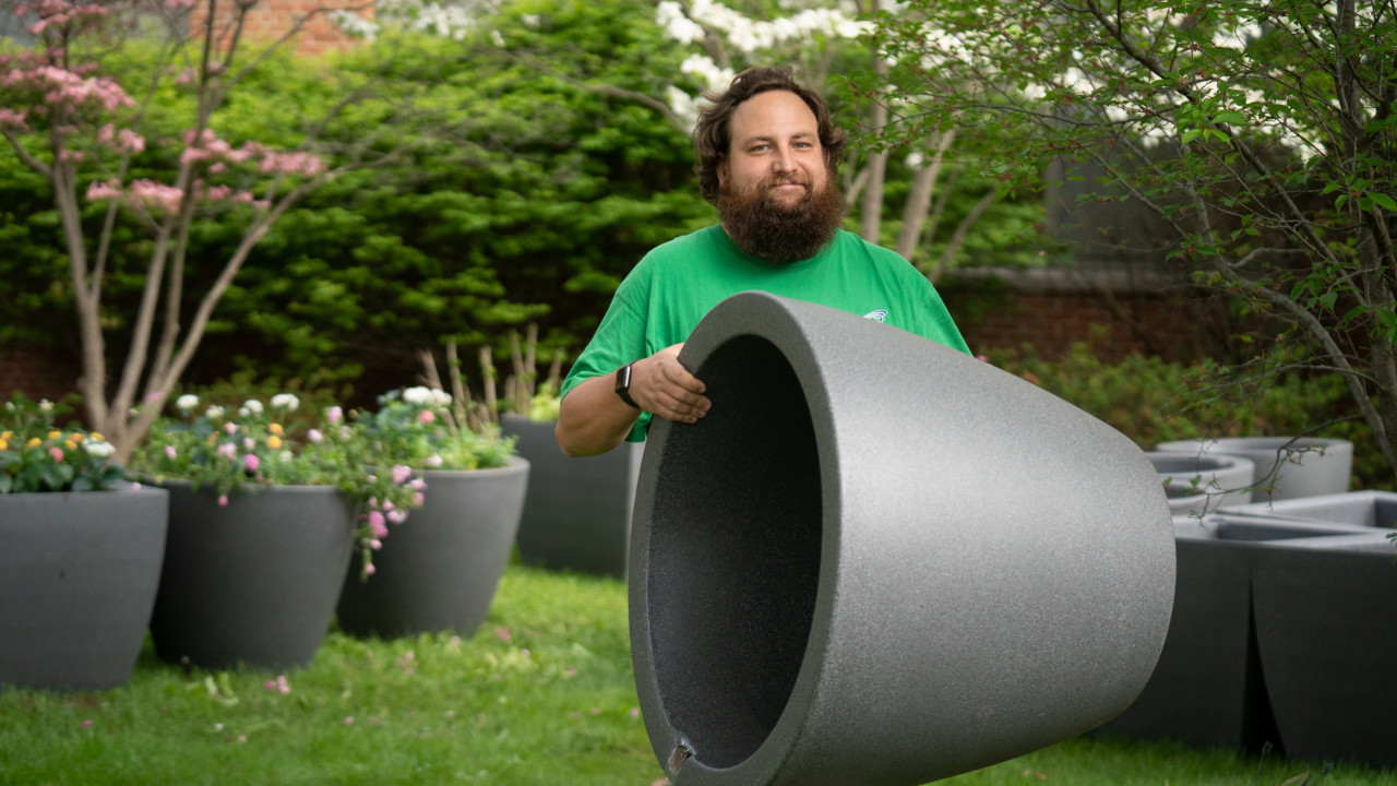 Landscape Services employee holds up an empty self-watering planter with more planters in the grass in the background