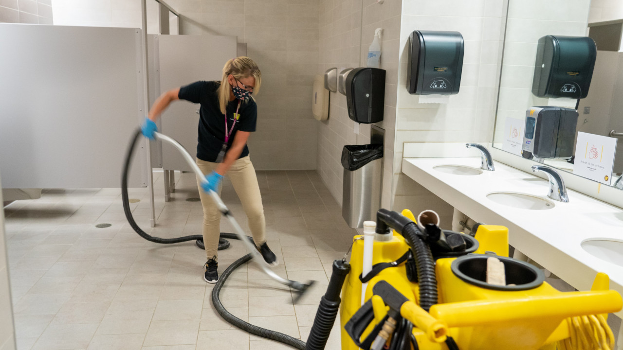 Employee uses machine to clean the floor of the restroom