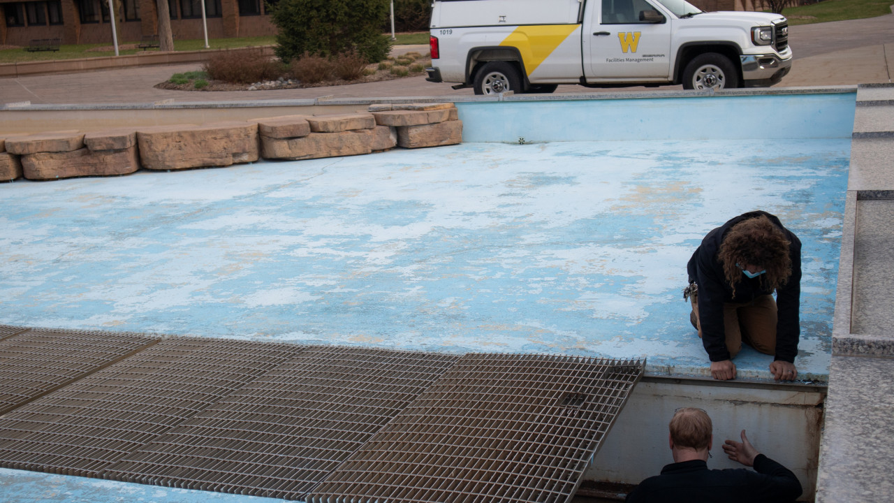Photo of two employees inside the Campus fountain, looking into the pit area under some grates with a maintenance truck in the background