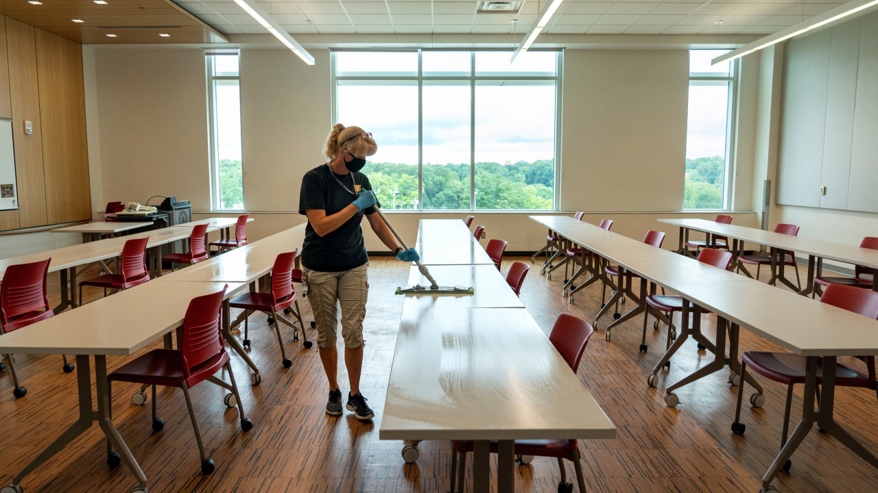 Employee cleans table in classroom with rows of tables and chairs