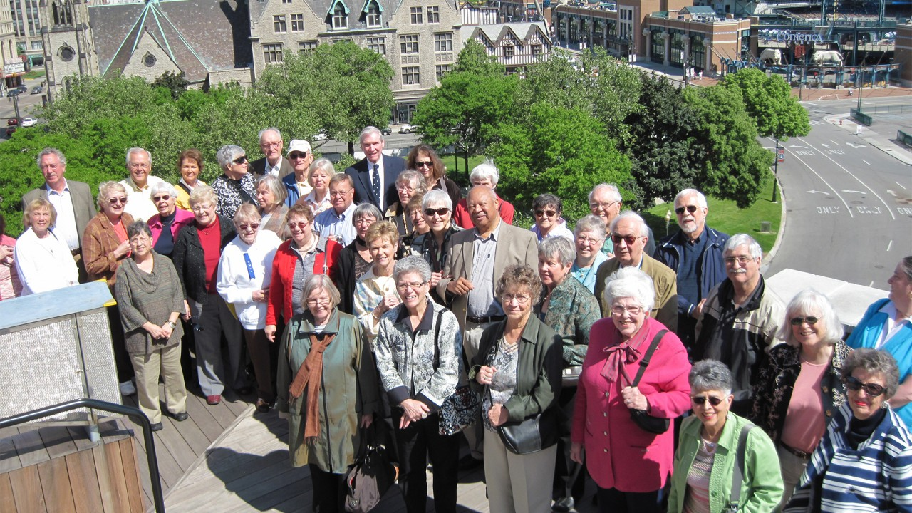 A group of Academy Lifelong Learning members pose for a photo while standing on a rooftop just outside of Comerica Park in Detroit, MI.