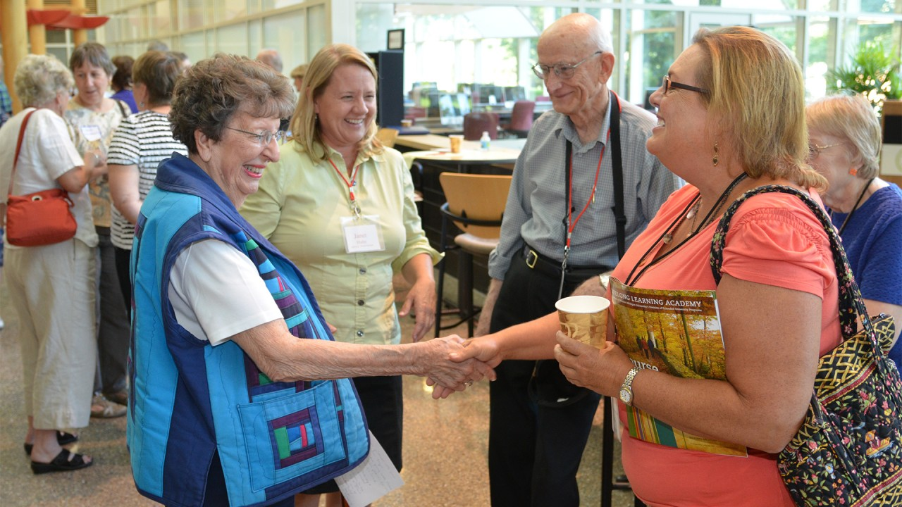 academy of lifelong learning members shake hands