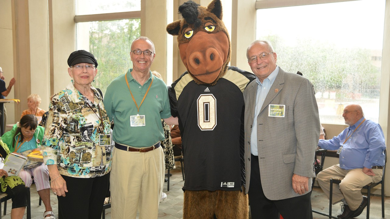 academy of lifelong learning members stand next to buster bronco