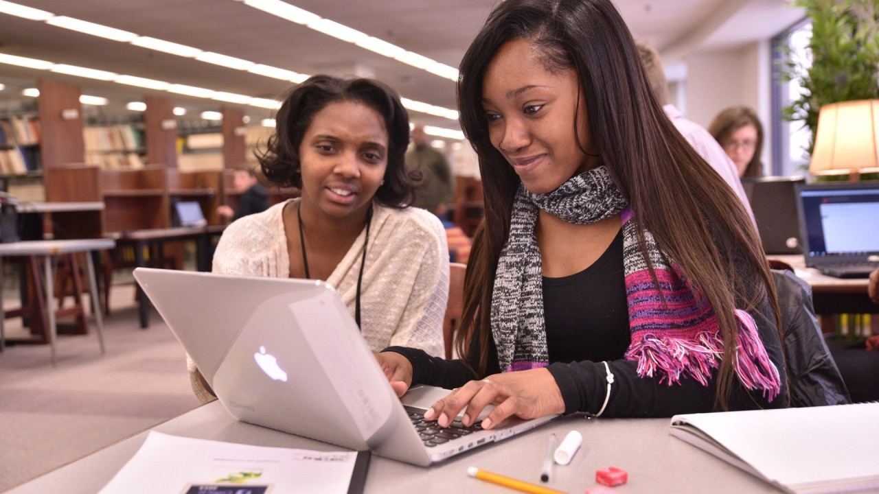Two students work together on a laptop in Waldo Library