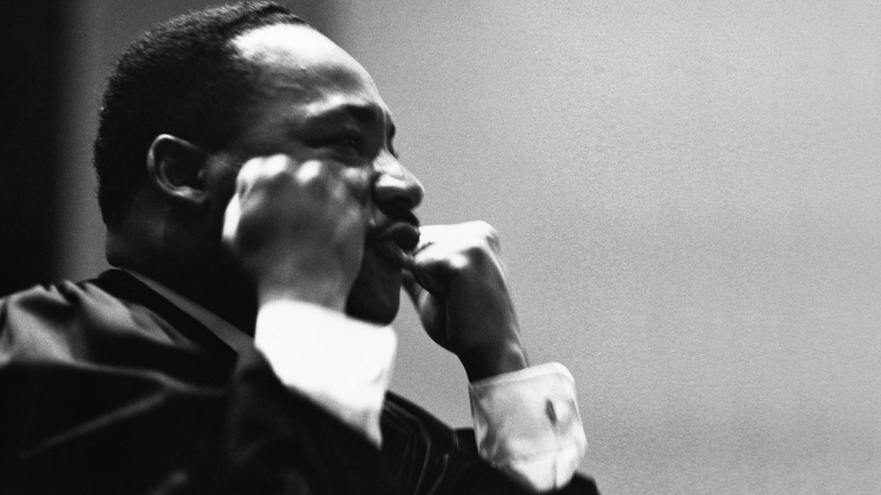 Reverend Dr. Martin Luther King stands with clenched hands while giving speech.