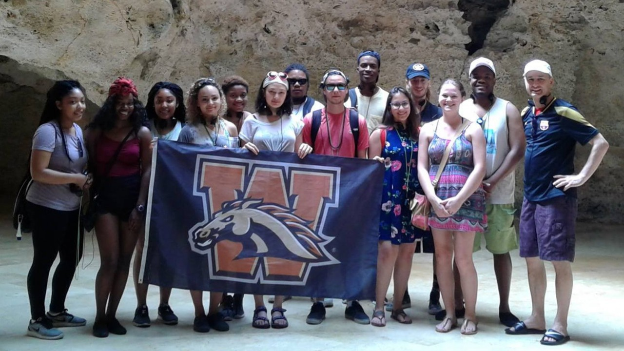 Kalamazoo Promise recipients hold WMU flag in the Dominican Republic