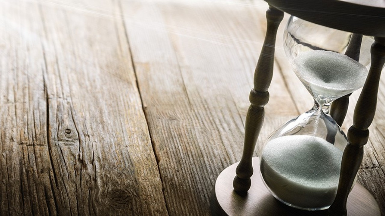 Picture shows an hourglass sitting on a weathered wooden floor.