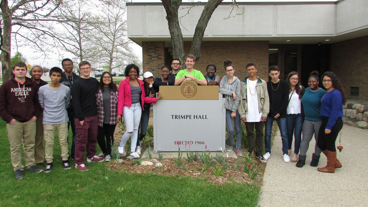 First-year Kalamazoo Promise Scholars stand around the Adrian Trimpe building sign
