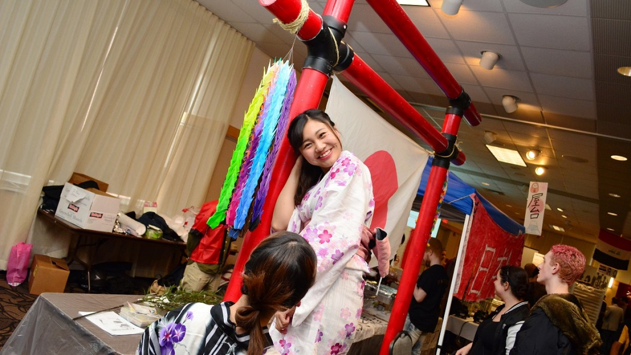 A Japanese student proudly shows off the Japanese Club's display at the 2017 International Festival.