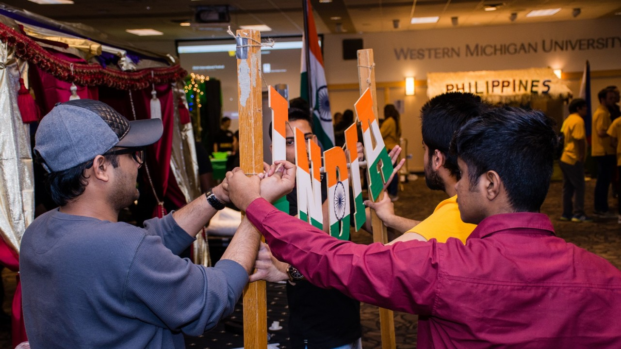"Four students work together to hang an ""India"" sign above their booth at the 2018 International Festival."