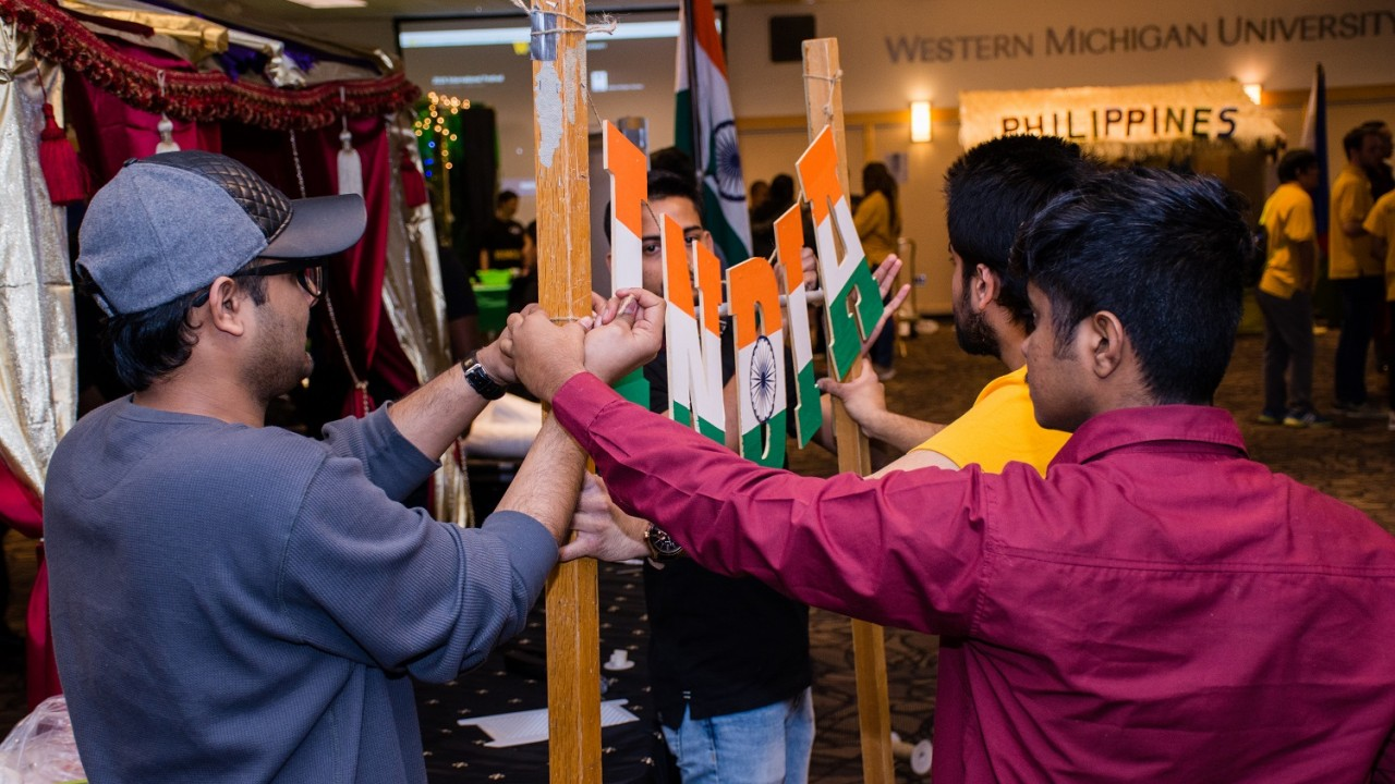"""Four students work together to hang an """"India"""" sign above their booth at the 2018 International Festival."""