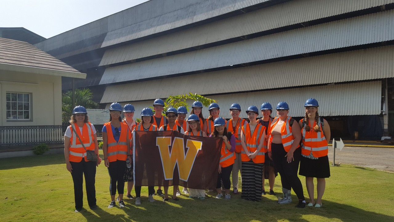 Students visit hold the W flag wearing hard hats and orange vests while visiting a sugar cane manufacturing facility.