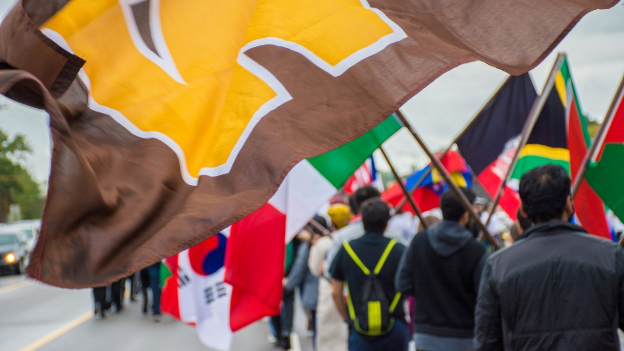 W Flag waves in foreground: international students carry flags from their home countries in background.