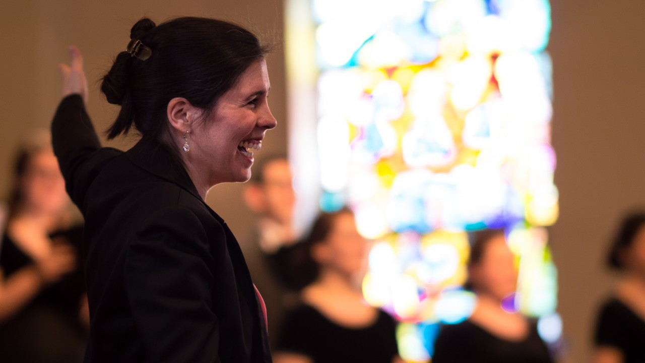 woman smiling in front of a choir and stain glass window