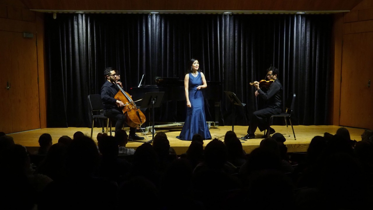 woman on stage singing with a cellist and violinist