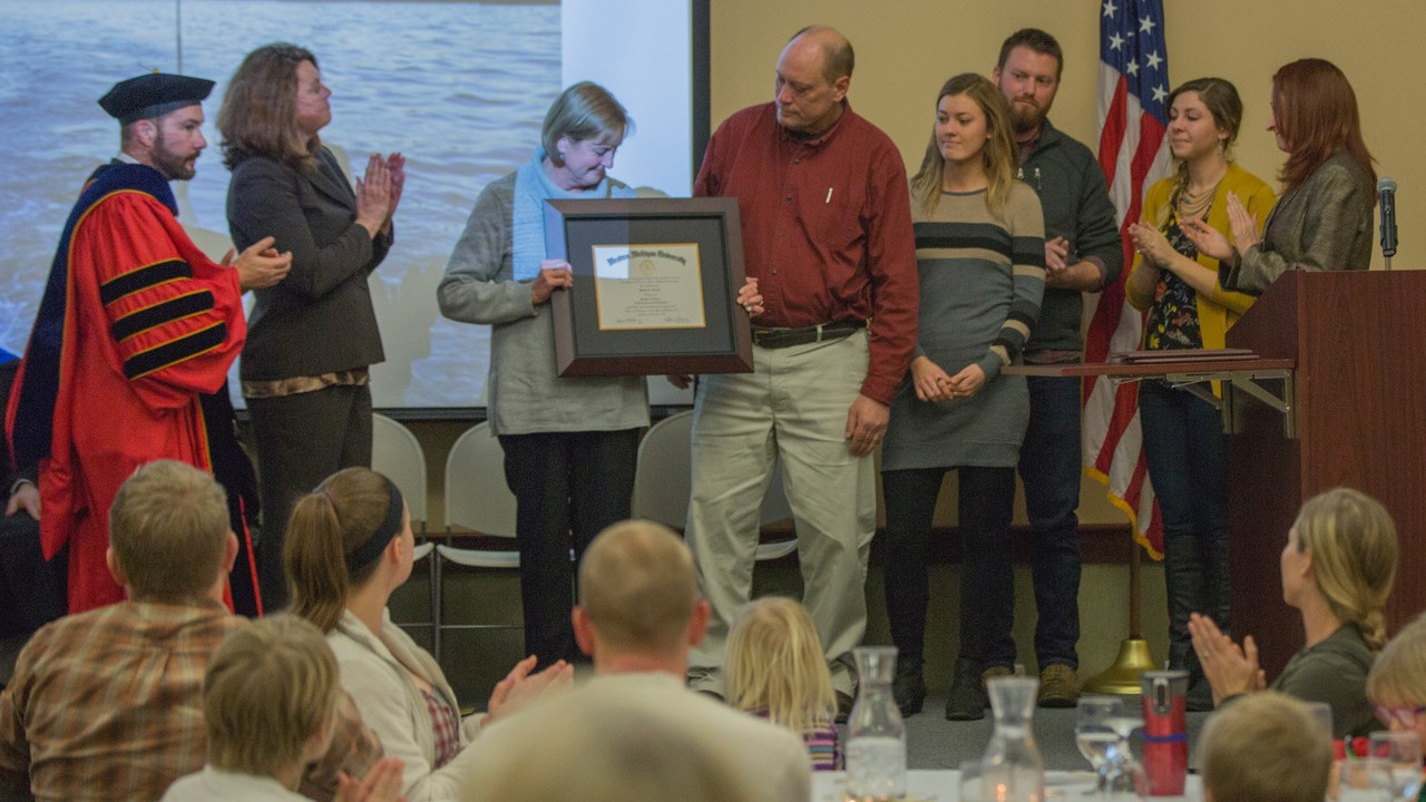 Michael Kandel's parents and siblings are presented with the diploma that was granted to Michael Kandel posthumously during Western Michigan University-Traverse City's graduate recognition ceremony for the freshwater science and sustainability program, Dec. 14. Kandel, a student of the freshwater science and sustainability program passed away following a tragic accident in Sturgeon Bay, July 20, 2017. Pictured (left-right) Dr. Edwin Martini, associate dean; Dr.Dawn Fortin Mattoon, associate provost; Annette