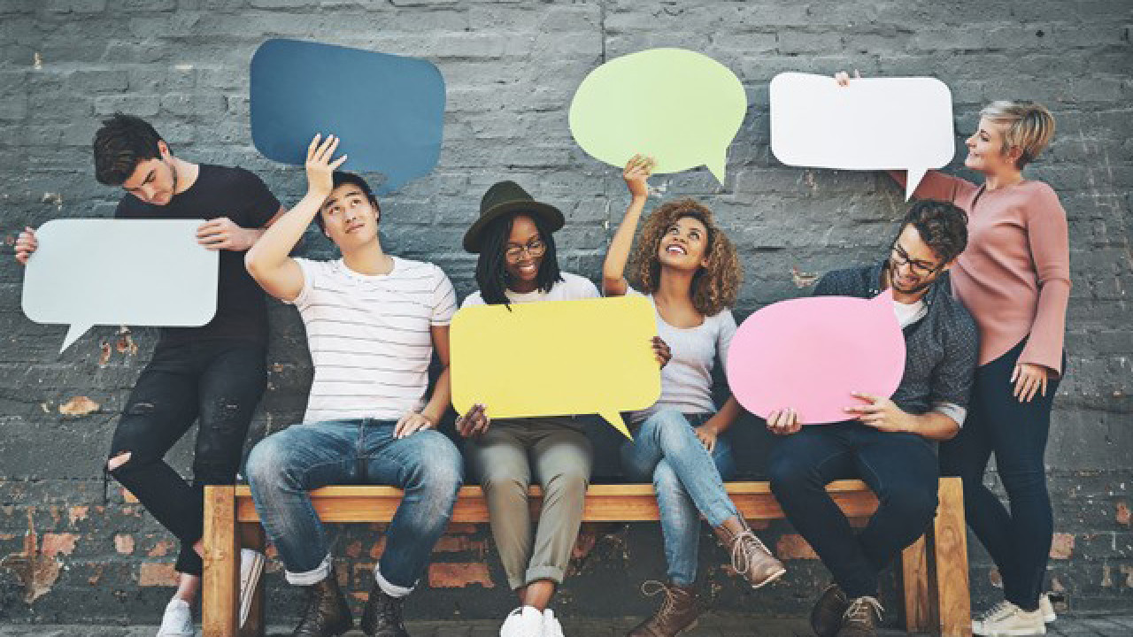 Students on a bench holding cardboard cutouts of speech bubbles.