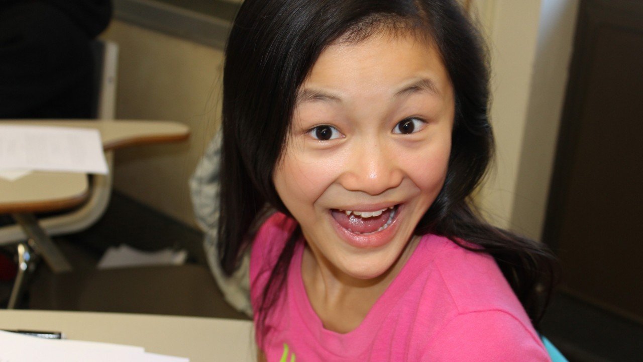 A young smiling girl in a student desk.