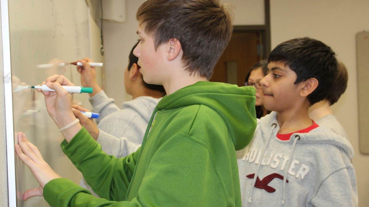 Photo of students writing on a dry erase board.