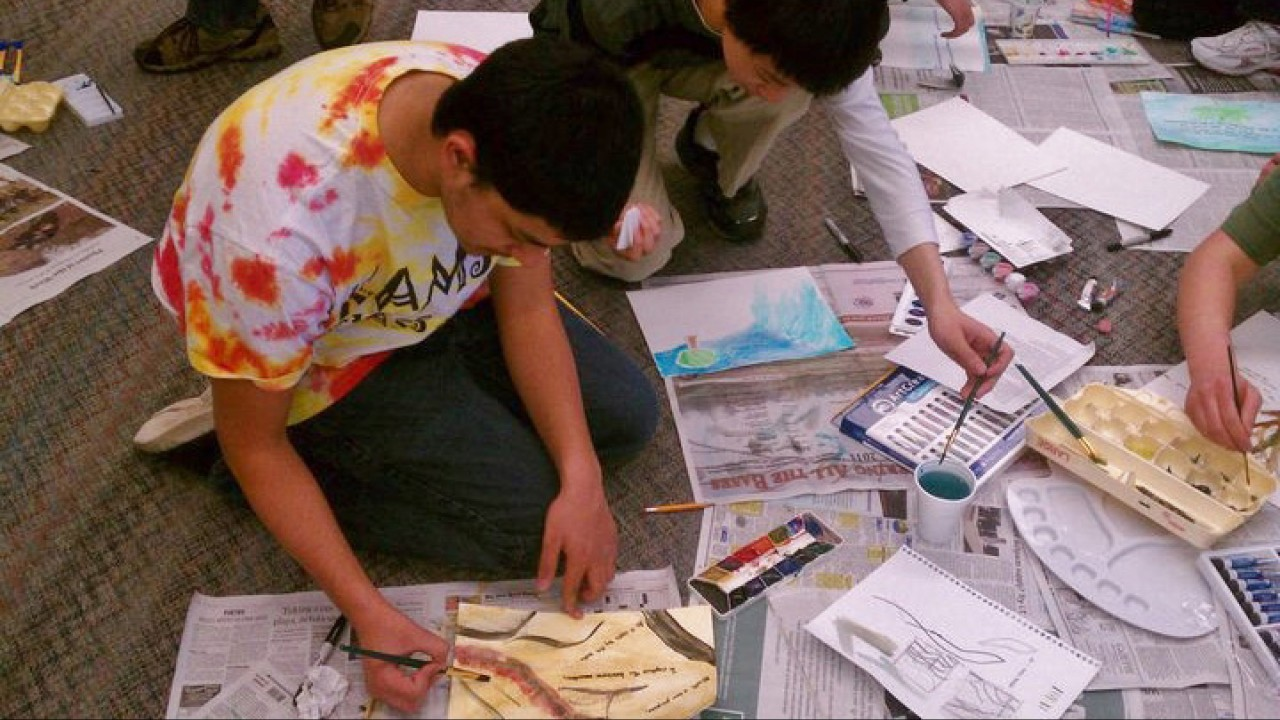 Students painting an art project on the floor.