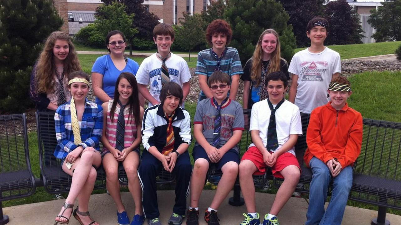 Students posing in two rows wearing ties.