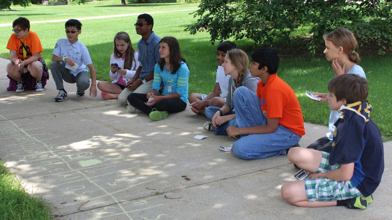 Students sitting on a sidewalk playing a game with chalk.