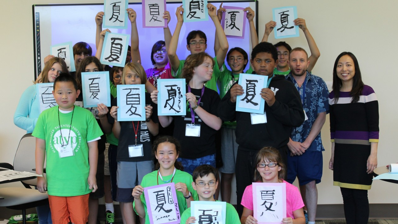 Students posing with calligraphy. wearing summer camp shirts.