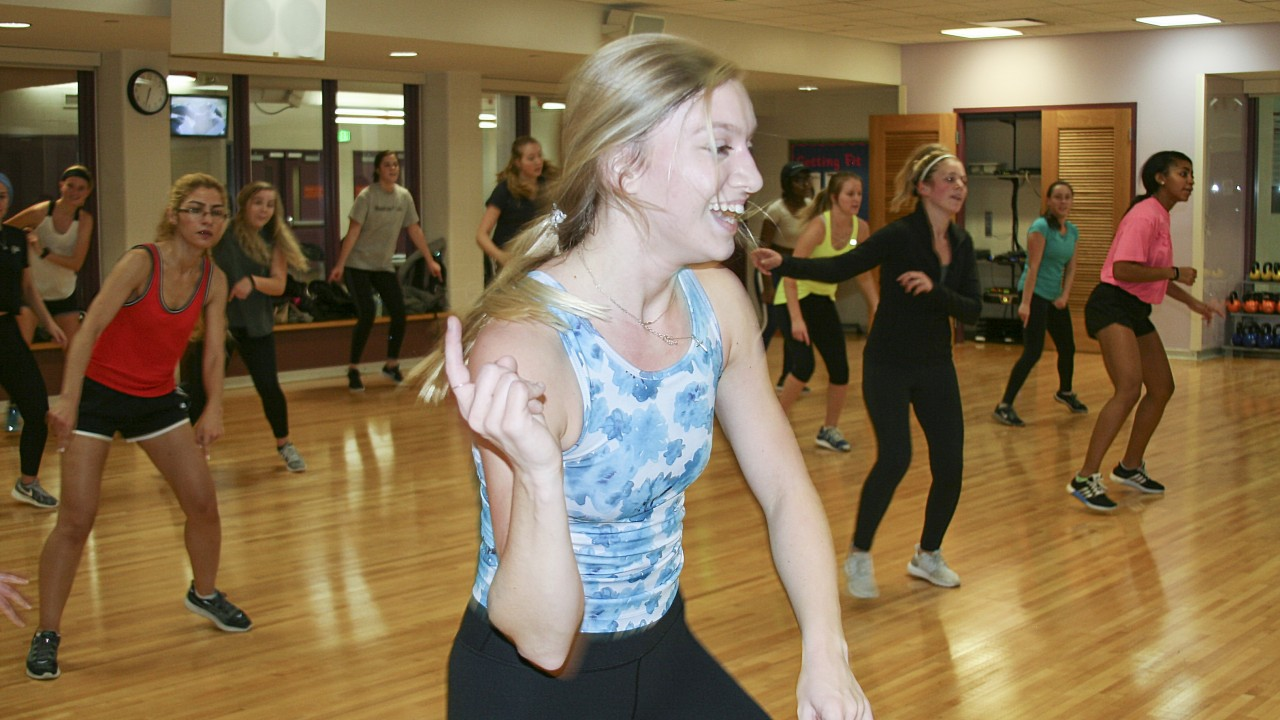 Group Fitness Instructor, Anna teaching Zumba class with diverse participants behind her.