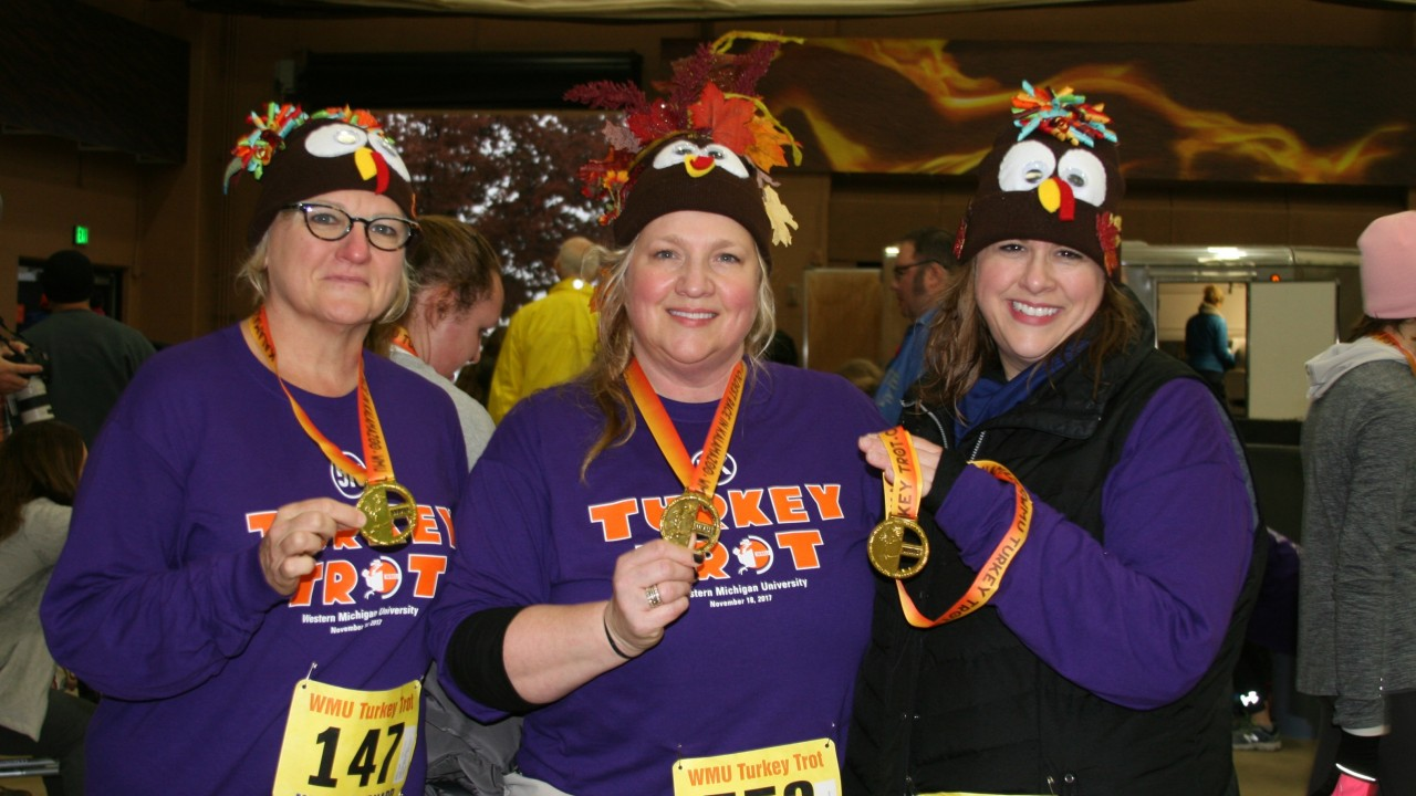 Three Turkey Trot participants wearing homemade turkey hats and holding their Turkey Trot medals.