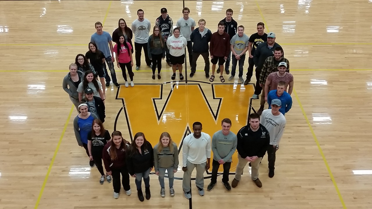 Sports Club Council members standing around the W on the gym floor of the SRC