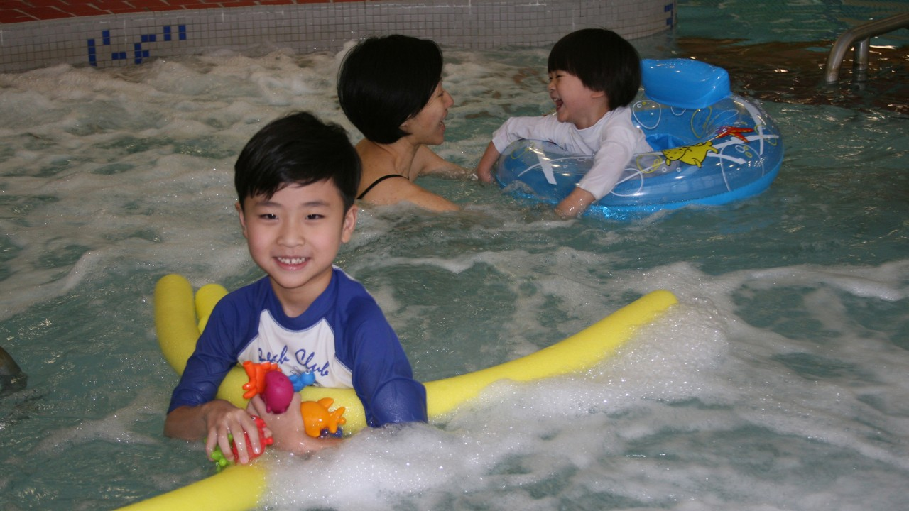 Child in pool smiling with a pool noodle. Mother and younger child in a swimming tube playing in the background.