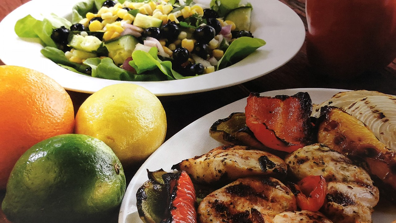 Chicken dish with a side dish of corn, greens and black beans. From Eat Real cookbook