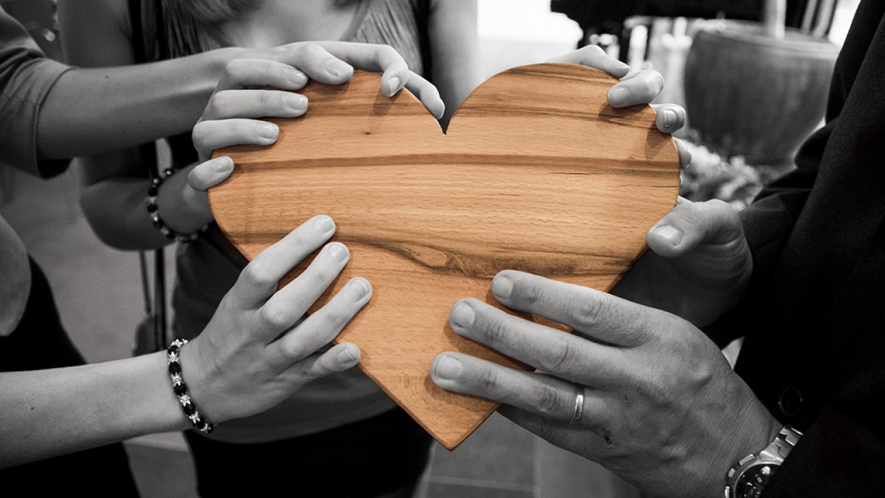 Different people's hands in black and white holding a wooden heart that is in color
