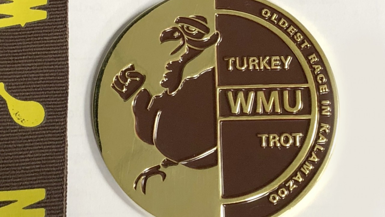 Photo of actual Turkey Trot medal that has the Turkey Trot logo on it