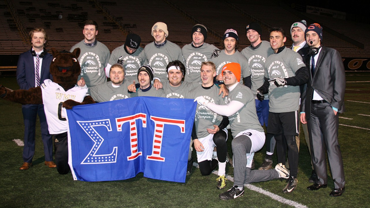 Sigma Tau Gamma Fraternity Flag Football Champion group photo, holding their fraternity flag with Buster Bronco